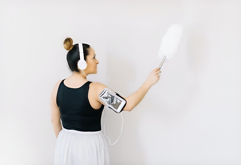 a women with headphones cleaning a wall with
