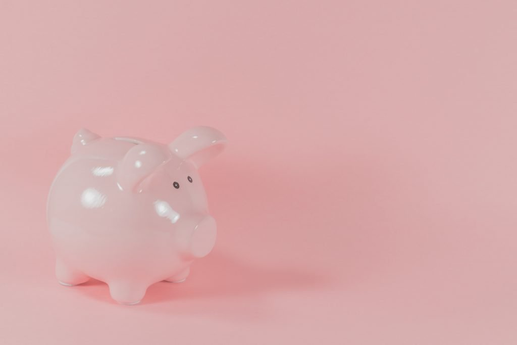 Small pink piggy bank on a pink background
